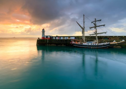 2AYKNR8 A tall ship and the lighthouse at the mouth of Newlyn Harbour captured at sunrise